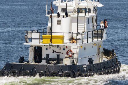 New Bedford, Massachusetts, USA - June 28, 2019: Stern view of tug Thuban crossing New Bedford harbor