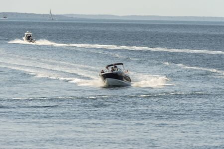 New Bedford, Massachusetts, USA - May 25, 2019: Powerboat making graceful turn crossing New Bedford outer harbor with Buzzards Bay in background