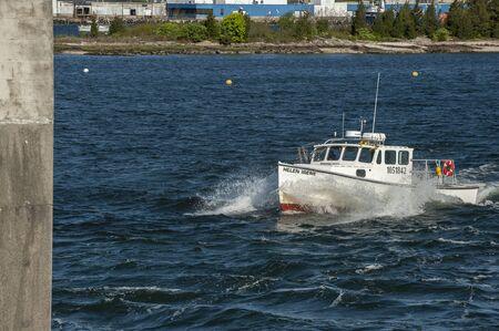 New Bedford, Massachusetts, USA - May 22, 2019: Lobster boat Helen Irene splashing through chop near hurricane barrier in New Bedford inner harbor Redakční