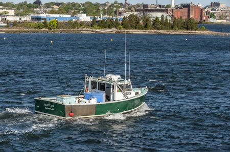 New Bedford, Massachusetts, USA - May 22, 2019: Lobster boat Reaction, hailing port Sandwich, Massachusetts, crossing New Bedford inner harbor