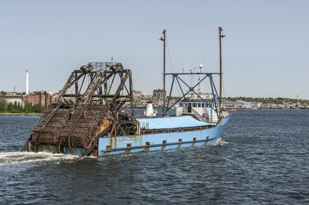New Bedford, Massachusetts, USA - June 3, 2019: Clammer E.S.S. Pursuit returning from trip with tarp covering clams