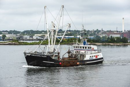 New Bedford, Massachusetts, USA - August 6, 2019: Eastern-rigged scalloper Christian & Alexa, hailing port Point Pleasant Beach, NJ, leaving New Bedford with new red and blue striping on wheelhouse