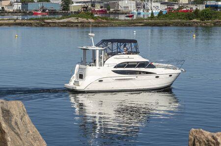 New Bedford, Massachusetts, USA - June 9, 2019: Motoryacht On Your Own V transiting New Bedford hurricane barrier