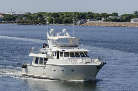 New Bedford, Massachusetts, USA - June 4, 2019: Motor yacht Java, hailing port Plymouth, Massachusetts, approaching New Bedford inner harbor