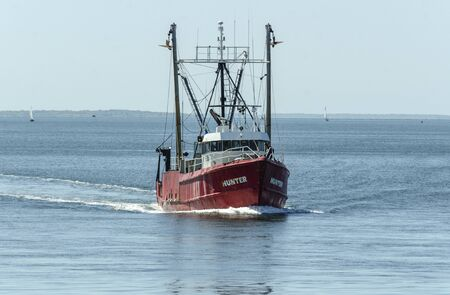 New Bedford, Massachusetts, USA - June 4, 2019: Commercial fishing boat Hunter crossing New Bedford outer harbor with Buzzards Bay in background Editorial