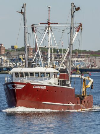 Fairhaven, Massachusetts, USA - June 4, 2019: Commercial fishing vessel Contender leaving Fairhaven with New Bedford waterfront in background