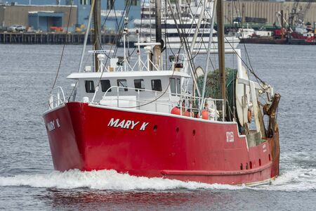 New Bedford, Massachusetts, USA - May 28, 2019: Dragger Mary K leaving port with New Bedford waterfront in background Redakční