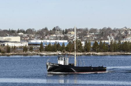 Fairhaven, Massachusetts, USA - April 2, 2019: Commercial fishing boat Maria Mendonsa leaving Fairhaven with New Bedford fish processing plants and hillside residential neighborhood in background