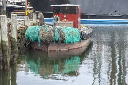 Green bow pudding on water tender reflecting off calm water in New England harbor Imagens