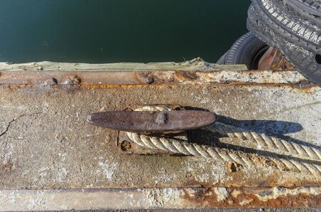 Rusty horn cleat anchoring dockline to commercial fishing boat Imagens
