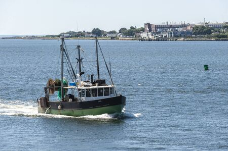 New Bedford, Massachusetts, USA - August 12, 2019: Trawler Lual passing factories along the New Bedford shoreline  on return from fishing trip