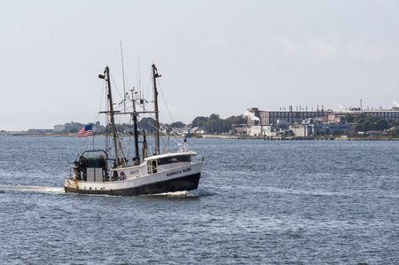 New Bedford, Massachusetts, USA - August 19, 2019: Commercial fishing boat Rebecca Mary, hailing port South Kingstown, Rhode Island, crossing New Bedford outer harbor