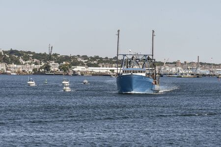 New Bedford, Massachusetts, USA - August 24, 2019: Cluster of small boats maintain their distance from clammer E.S.S. Pursuit on Acushnet River