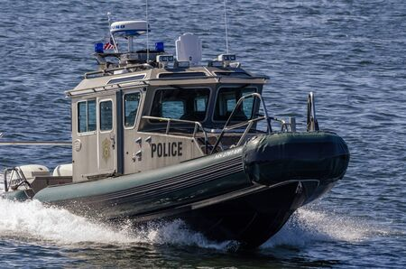 New Bedford, Massachusetts, USA - August 24, 2019: Massachusetts Environmental Police patrol boat nearing hurricane barrier on Acushnet River Editorial
