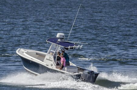 New Bedford, Massachusetts, USA - August 30, 2019: Woman passenger smiling at camera as center console boat accelerates away from New Bedford hurricane barrier Editorial