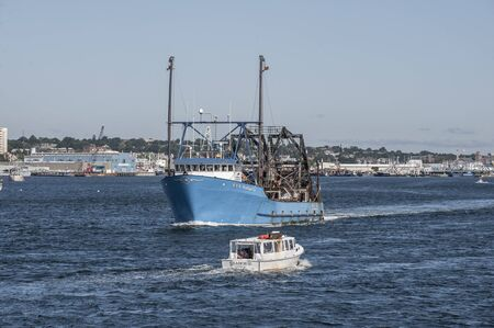 New Bedford, Massachusetts, USA - September 3, 2019: Cuttyhunk water taxi Seahorse passing clammer E.S.S. Pursuit in New Bedford harbor