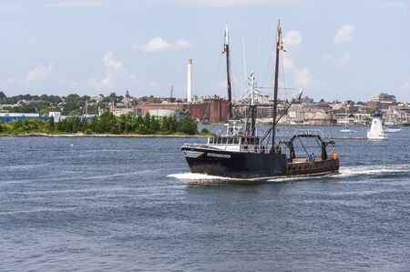 New Bedford, Massachusetts, USA - August 19, 2019: Commercial fishing boat Determination leaving New Bedford to go fishing.