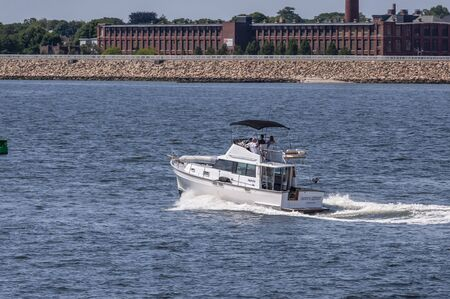 New Bedford, Massachusetts, USA – July 27, 2019: Motor yacht Pappys Retreat, hailing port Plymouth, Massachusetts, cruising across New Bedford outer harbor with hurricane barrier and factory in background