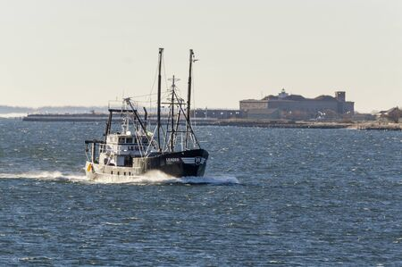 New Bedford, Massachusetts, USA - January 7, 2019: Eastern rig commercial fishing boat Leader, hailing port Cape May, New Jersey, sporting thin layer of ice as she heads into New Bedford on windy winter morning