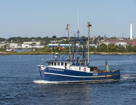 New Bedford, Massachusetts, USA - September 21, 2019: Commercial fishing boat Tom Slaughter II, hailing port Gloucester, Massachusetts, heading to sea with New Bedford waterfront in background Redakční
