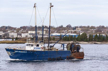 New Bedford, Massachusetts, USA - November 7, 2019: Commercial fishing boat Sao Marcos II crossing Acushnet River with New Bedford waterfront in background