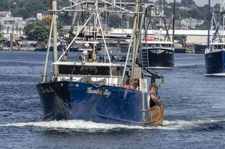 New Bedford, Massachusetts, USA - August 27, 2019: Dragger Thunder Bay at head of commercial fishing boats leaving port