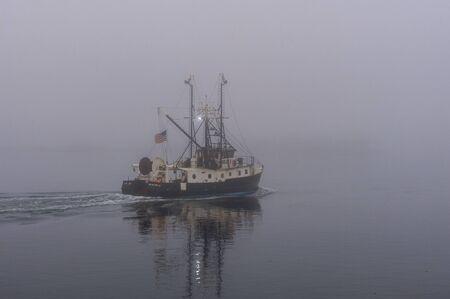 New Bedford, Massachusetts, USA - November 27, 2019: Stern view of commercial fishing boat Capt. John crossing New Bedford inner harbor on foggy morning