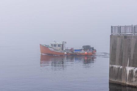 New Bedford, Massachusetts, USA - November 27, 2019: Lobster boat transiting New Bedford hurricane barrier on foggy morning