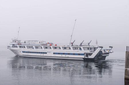 New Bedford, Massachusetts, USA - November 27, 2019: Cruise boat Grande Mariner transiting New Bedford hurricane barrier on foggy morning