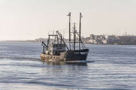 New Bedford, Massachusetts, USA - November 26, 2019: Commercial fishing vessel Leader, hailing port Cape May, New Jersey, approaching New Bedford on hazy morning