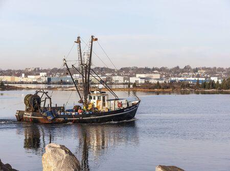 New Bedford, Massachusetts, USA - November 26, 2019: Commercial fishing boat Mattie and Maren, hailing port Point Judith, Rhode Island, crossing New Bedford inner harbor