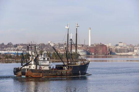 New Bedford, Massachusetts, USA - November 26, 2019: Commercial fishing boat Leader, hailing port Cape May, New Jersey, crossing New Bedford inner harbor