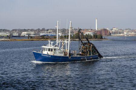 New Bedford, Massachusetts, USA - November 25, 2019: Clammer Madison III, hailing port Atlantic City, New Jersey, crossing New Bedford inner harbor on her way to sea