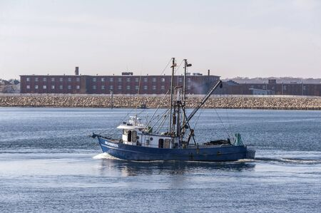 New Bedford, Massachusetts, USA - November 25, 2019: Clammer Silverfox crossing New Bedford outer harbor on her way to sea