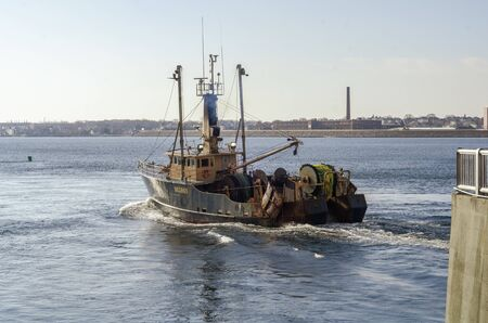 New Bedford, Massachusetts, USA - November 25, 2019: Commercial fishing boat Morue crossing New Bedford outer harbor on her way to sea