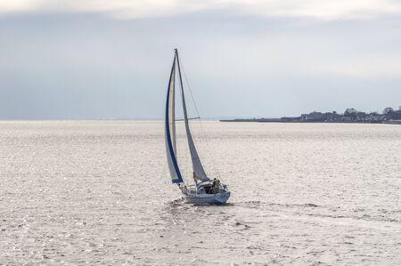 New Bedford, Massachusetts, USA - November 15, 2019: Sailboat Va Pensiero, hailing port Boston, Massachusetts,  crossing New Bedford outer harbor on her way into Buzzards Bay