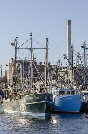 New Bedford, Massachusetts, USA - November 30, 2019: Commercial fishing boats Seven Seas and Angel Fisher with old power plant in background
