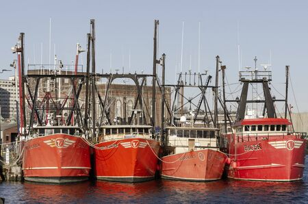New Bedford, Massachusetts, USA - November 30, 2019: Line of commercial fishing boats docked at Pier 3