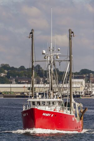 New Bedford, Massachusetts, USA - June 17, 2019: Brightly colored dragger Mary K glowing against New Bedford background
