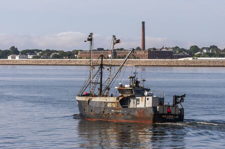New Bedford, Massachusetts, USA - July 26, 2019: Eastern rig scalloper William Lee crossing New Bedford outer harbor with factory in background 報道画像