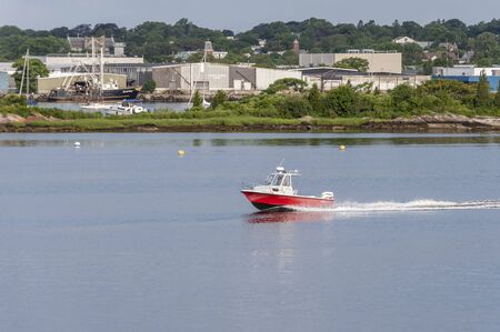 New Bedford, Massachusetts, USA - July 27, 2019: Men in powerboat cutting across New Bedford harbor 報道画像