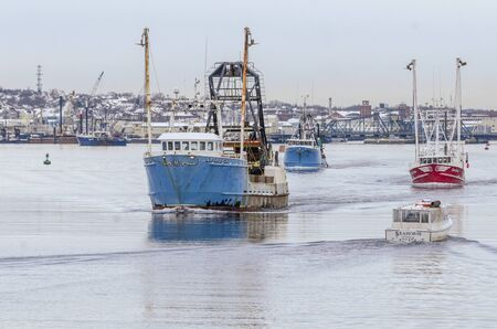 New Bedford, Massachusetts, USA - December 4, 2019: Cuttyhunk water taxi Seahorse works her way past outbound cluster of commercial fishing boats