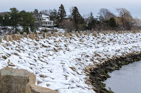 Huricane protection barrier layered with snow curving across Acushnet River at Fort Phoenix in Fairhaven, Massachusetts