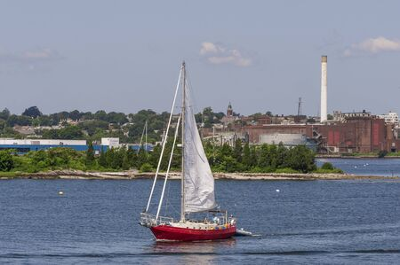 New Bedford, Massachusetts, USA - July 26, 2019: Sailor guiding sailboat out of New Bedford inner harbor 報道画像