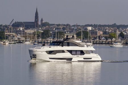 Fairhaven, Massachusetts, USA - July 26, 2019: Motoryacht Golden Eye leaving Fairhaven with New Bedford waterfront in background. Editorial use only.