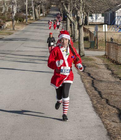 Mattapoisett, Massachusetts, USA - December 7, 2019: Young woman Santa strung with lights heading for finish line of Mattapoisett Santa 5K Run. Editorial use only. 報道画像