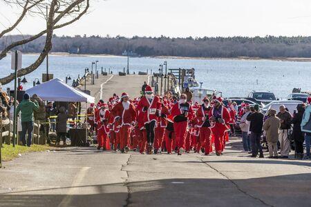 Mattapoisett, Massachusetts, USA - December 7, 2019: Horde of Santas take on harborside uphill start of Mattapoisett Santa 5K Run. Editorial use only.