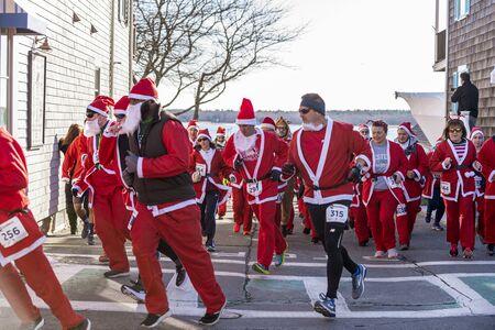 Mattapoisett, Massachusetts, USA - December 7, 2019: Cluster of Santas making turn at start of Mattapoisett Santa 5K Run. Editorial use only. 報道画像