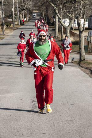 Mattapoisett, Massachusetts, USA - December 7, 2019: Colorful Santa leading horde of runners to finish of Mattapoisett Santa 5K Run. Editorial use only.