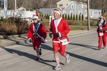 Mattapoisett, Massachusetts, USA - December 7, 2019: Group of running Santas heading for finish line of Mattapoisett Santa 5K Run. Editorial use only.